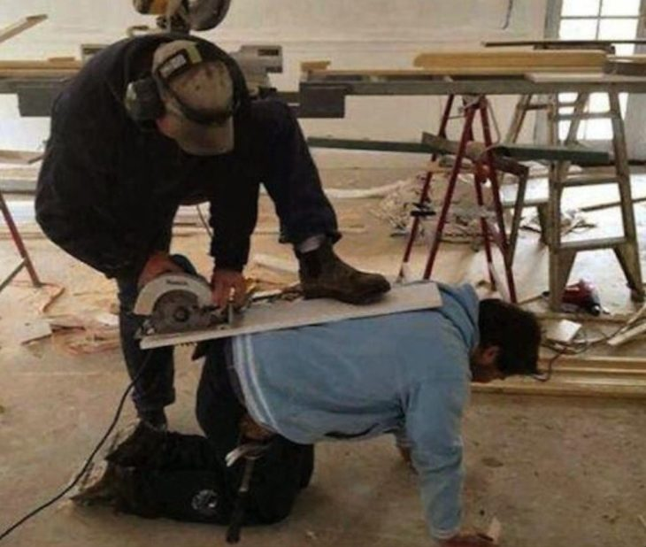 señor utiliza una sierra eléctrica en la espalda de un hombre