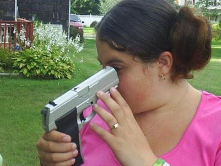 mujer apuntando a su ojo con una pistola