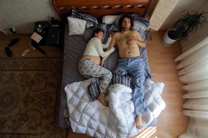 pareja de embarazados durmiendo en cuarto pequeño