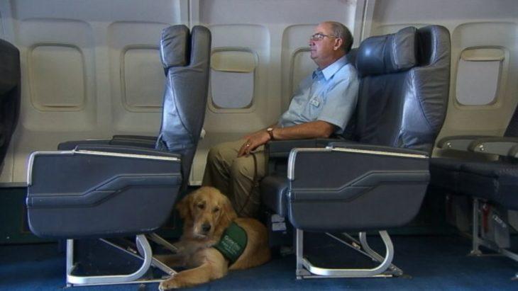 señor con su perro en un avión