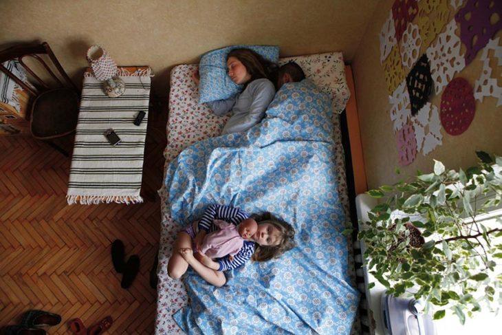 pareja de embarazados con una niña duermen