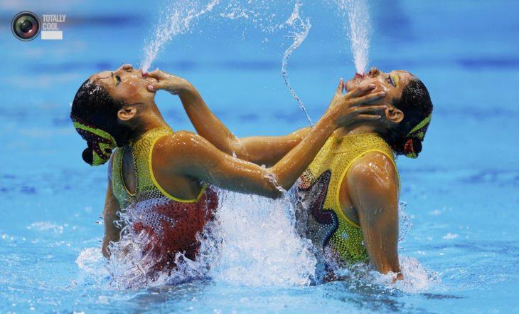 mujeres escupiendo agua