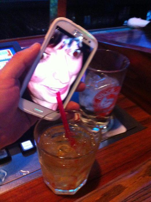 Mujer tomando de vaso en celular