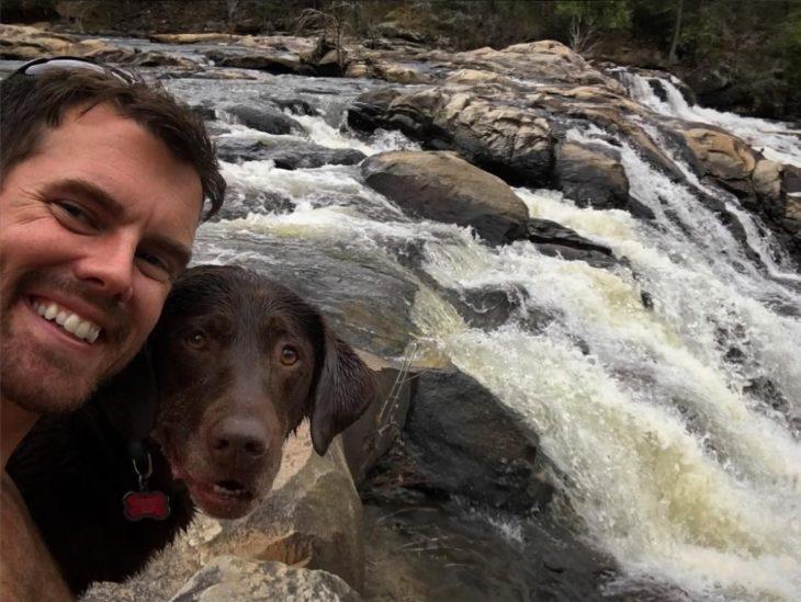 Selfie de hombre y su perra en una cascada