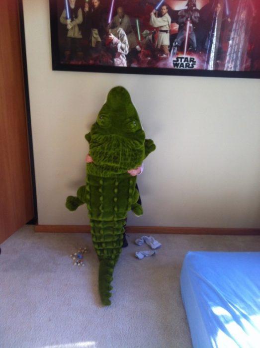 Niño escondido atrás de un cocodrilo de peluche