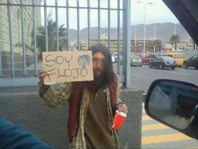 Un vagabundo pidiendo dinero con unletrero que dice soy flojo