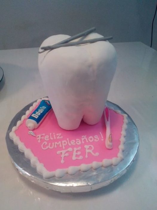 Pastel de un diente con pasta dental y un cepillo de dientes al lado