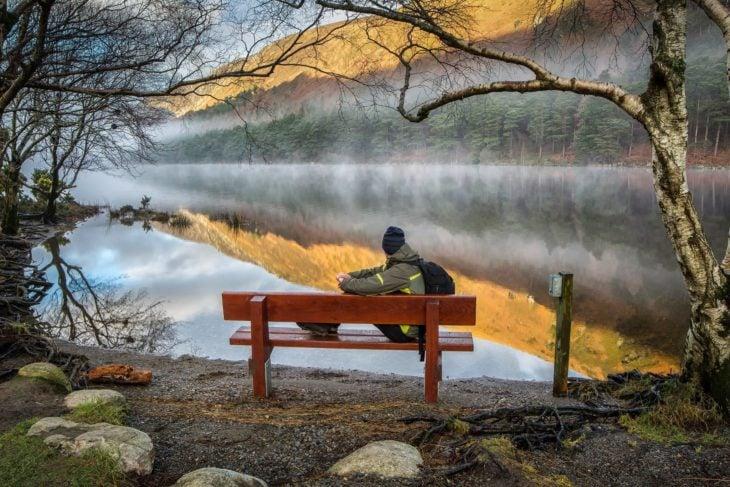 hombre sentado frente a un lago