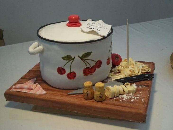 pastel de una olla con masa al lado, un cuchillo y salero y pimientero y una toalla
