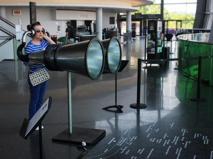 Mujer en lo que parece un aeropuerto escuchando algo en unos binoculares gigantes