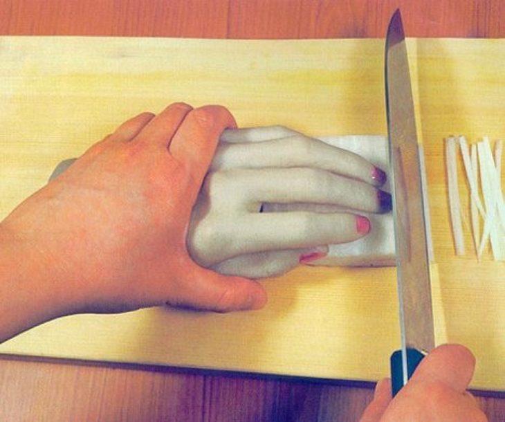 Persona sosteniendo una mano de plastico que a la vez sostiene una barra de algo que se està cortando con un cuchillo