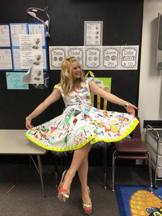 maestra de preescolar enseña un vestido dibujado por sus alumnos