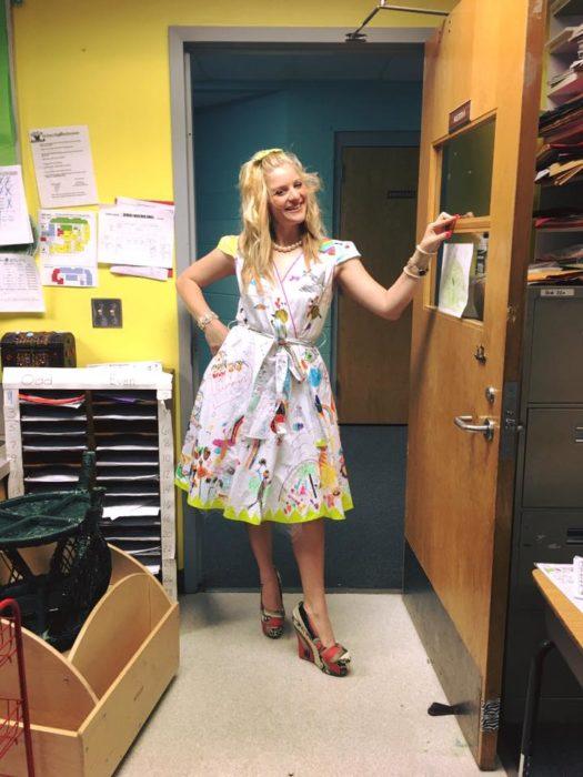 maestra de kinder en la puerta con un vestido dibujado por sus alumnos
