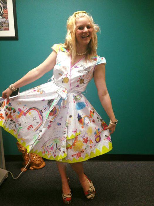 maestra de jardín de niños posa con un vestido dibujado por sus alumnos