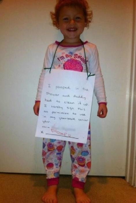 Una niña con un letrero colgando de su cuello