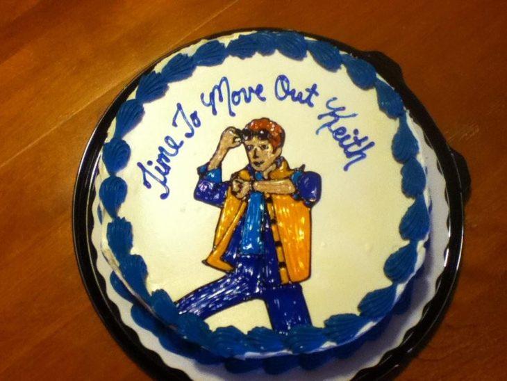 Un pastel con un muñeco y el texto diciendo que es hora de mudarse