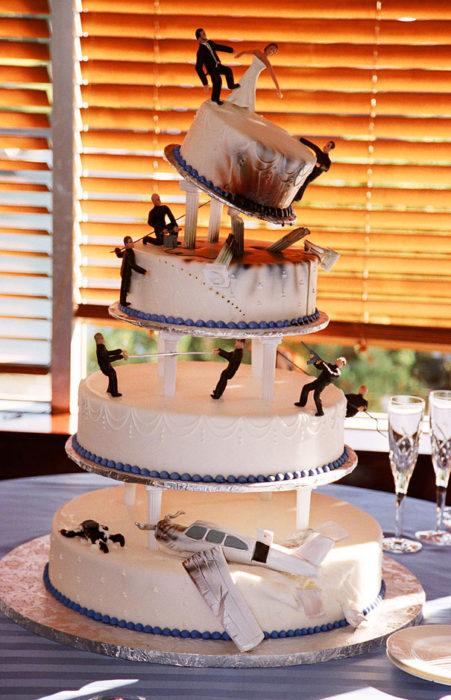 Pastel de bodas con muñequitos de acción y una avioneta derribada en la parte de abajo