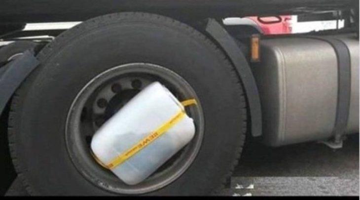 Recipiente con agua y ropa adentro amarrado en una llanta d eun trailer