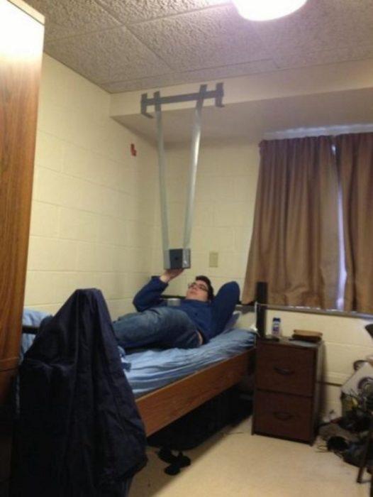 Hombre acostado en la cama y viendo su tablet que está colgando del techo pegada con cinta