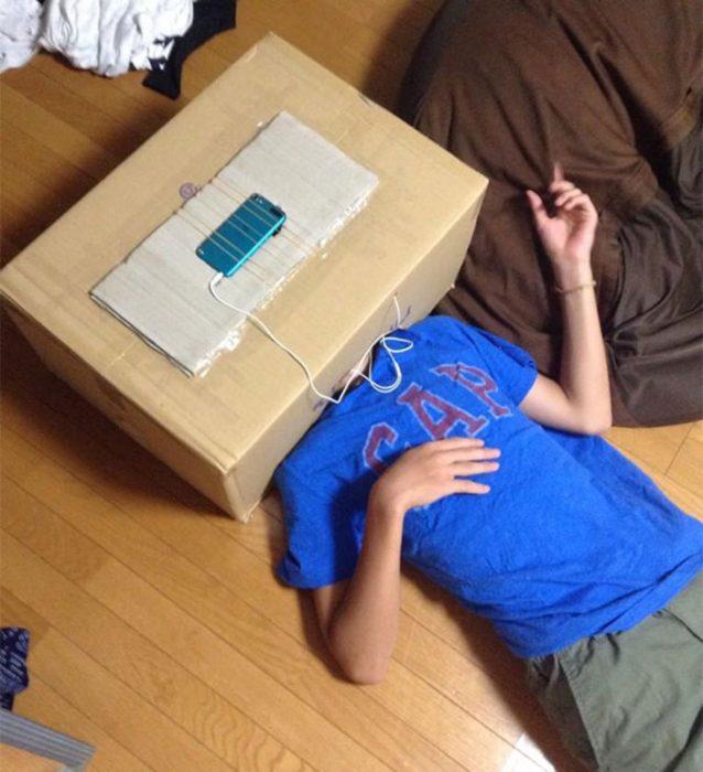 Joven acostado en el piso con una caja encima de su cabeza y un hoyo para ver su celular