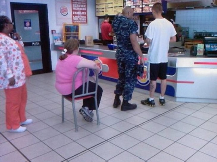 Mujer en la fila de burger king sentada en una silla