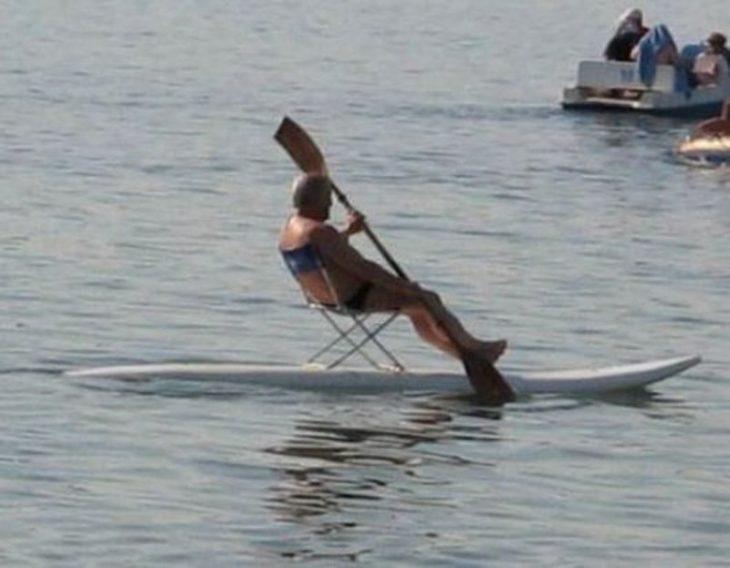 Hombre sentado en una silla arriba de una tabla de surf