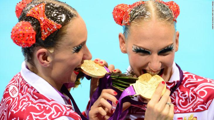 dos mujeres mordiendo sus medallas