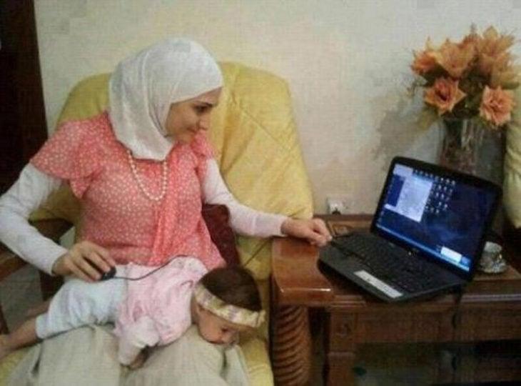 mujer musulmana con el mouse sobre su bebé