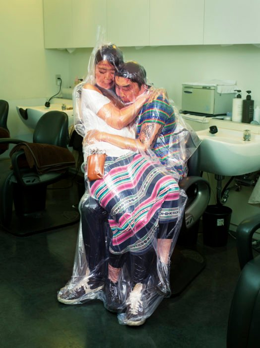 Hombre japonés con mujer en sus brazos envueltos en una bolsa de plástico