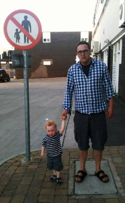 hombre y niño parados al lado de señal que prohibe hombre y niño de la mano