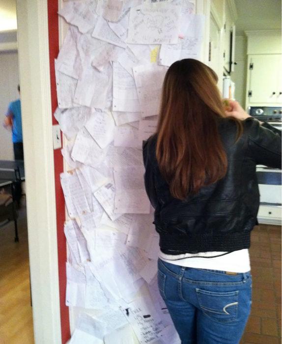 mujer poniendo papeles en una puerta