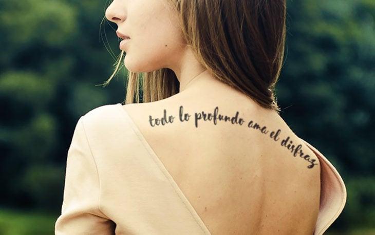 mujer con frase tatuada en la espalda