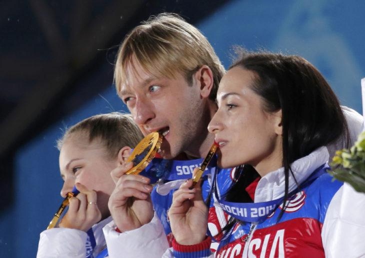 3 atletas mordiendo sus medallas