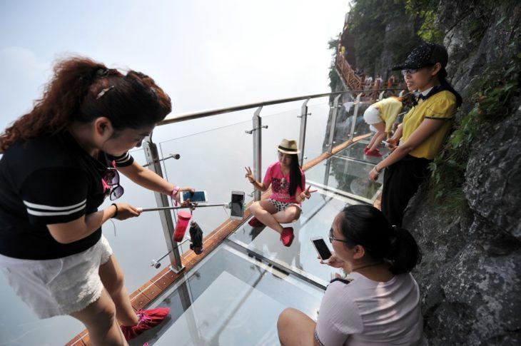 chica tomándose una foto en un puente de vidrio