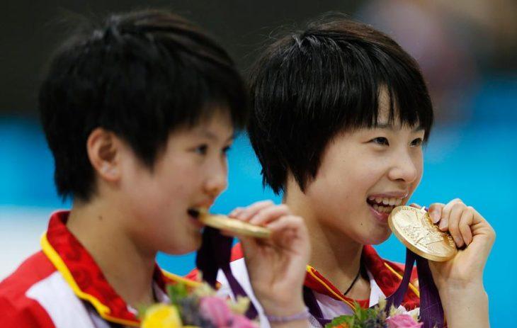 niños mordiendo medalla de oro