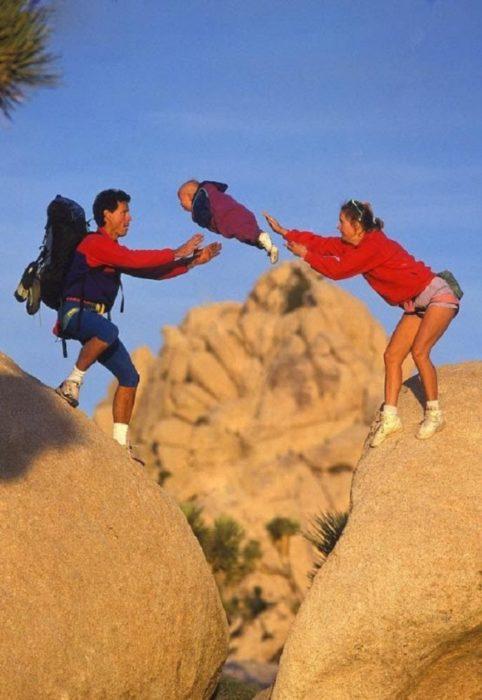 padres avientan a su hijo sobre las rocas