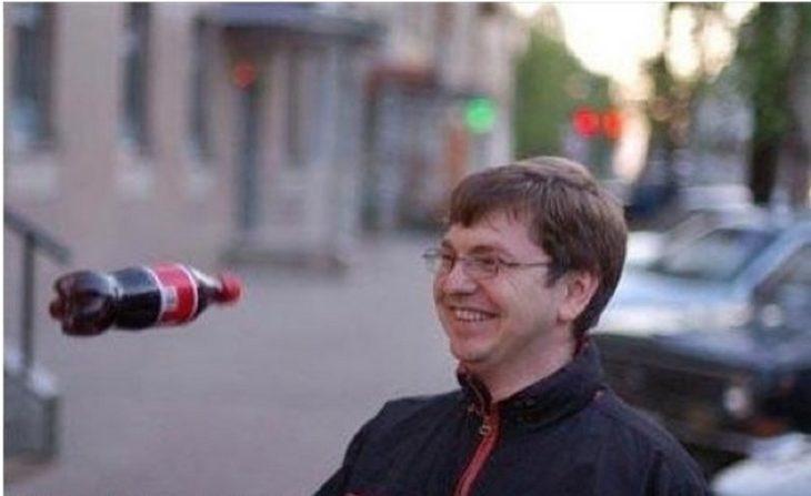 hombre sonrie mientras le arrojan una coca a la cara