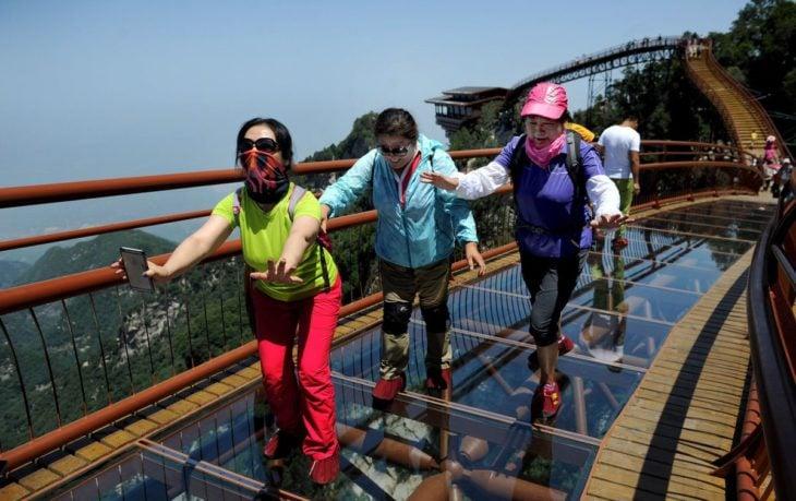 muchos turistas en un puente de vidrio
