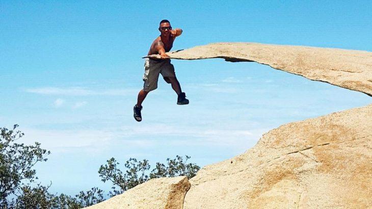 hombre apoyándose en una roca