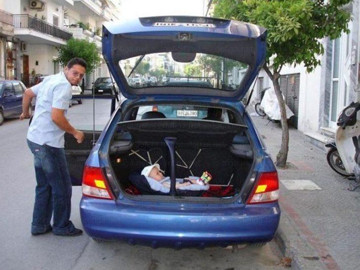 padre pone a su bebé en la cajuela del coche