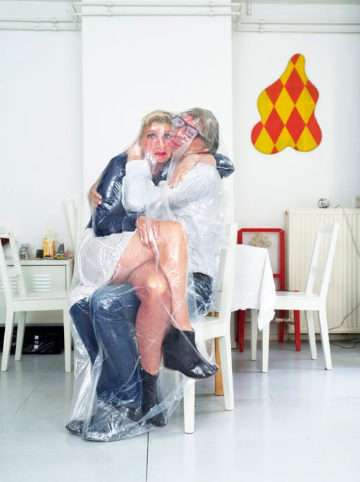 hombre con lentes y mujer en su regazo envueltos en una bolsa de plástico
