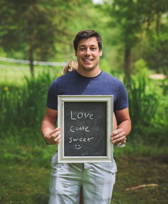 Hombre sostiene letrero que dice LOVE CUTE SWEET