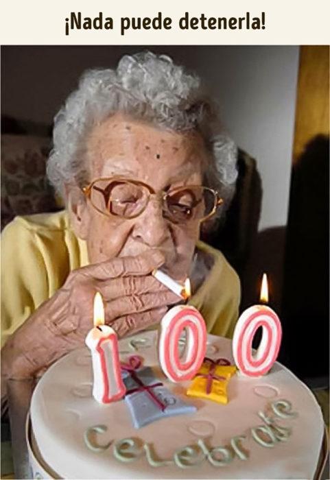 anciana prendiendo las velas de su cumpleaños con un cigarro