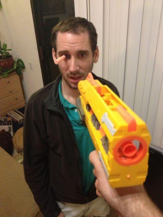 pistola de juguete dispara a hombre