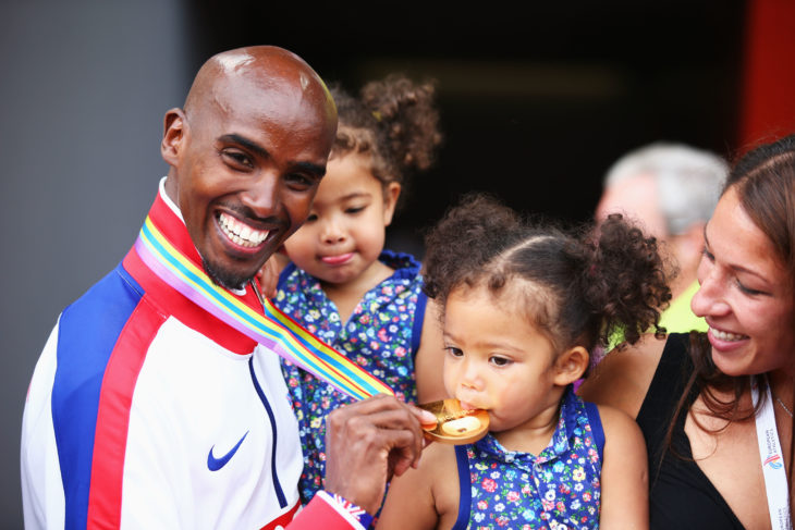 niña mordiendo medalla de su papá