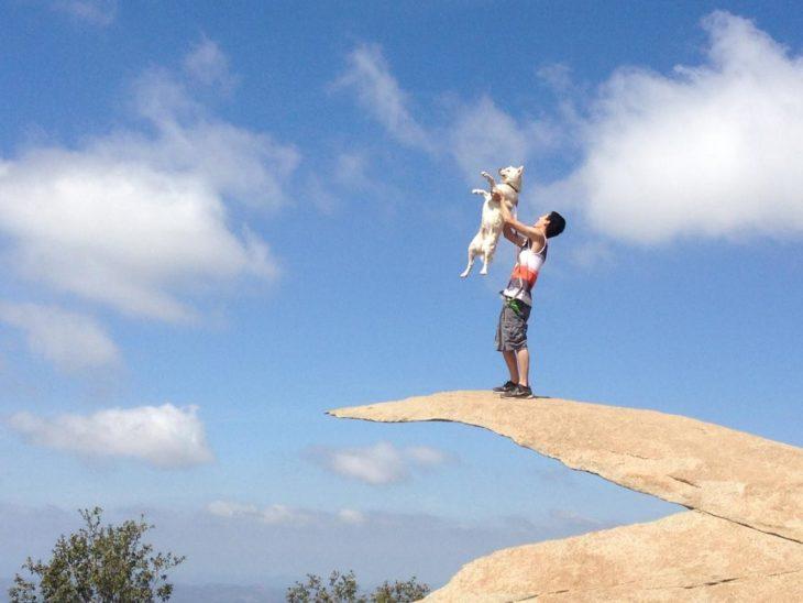 chico cargando un perro sobre una roca