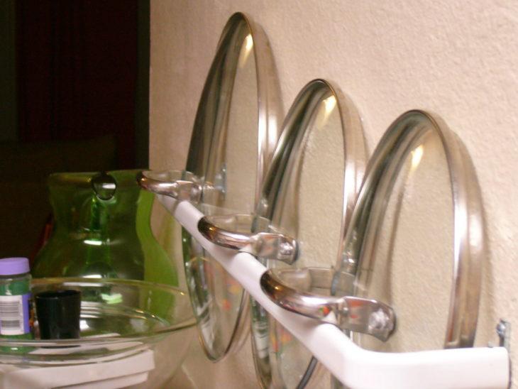 barra de baño sosteniendo tapas de sartenes