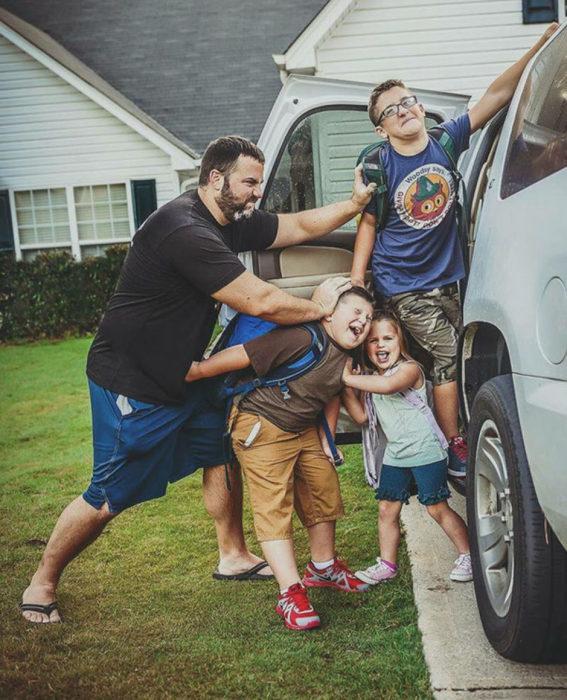 hombre mete a niños en un coche