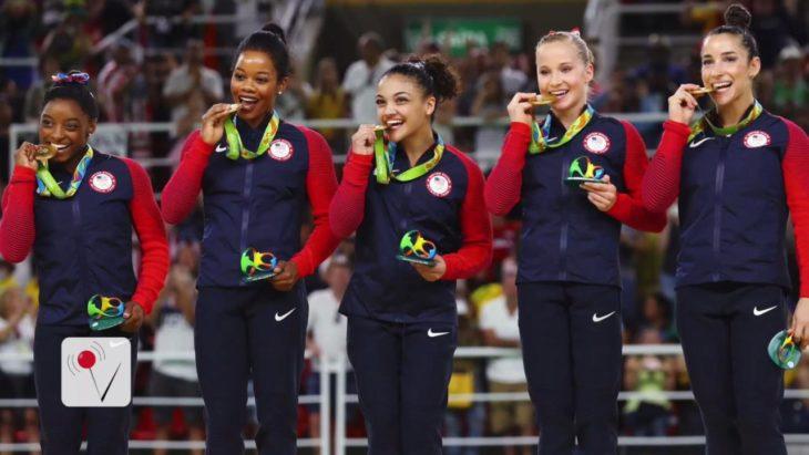 equipo femenino mordiendo medallas olímpicas
