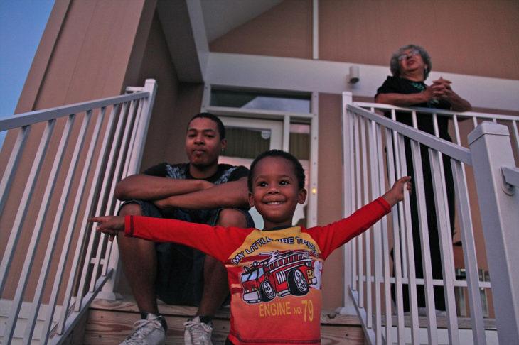 tres chicos frente a una casa